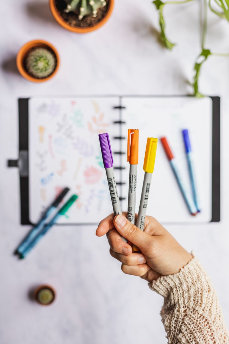 Hand holding erasable pens in purple, orange and yellow with open Asoki notebook and pens in the background