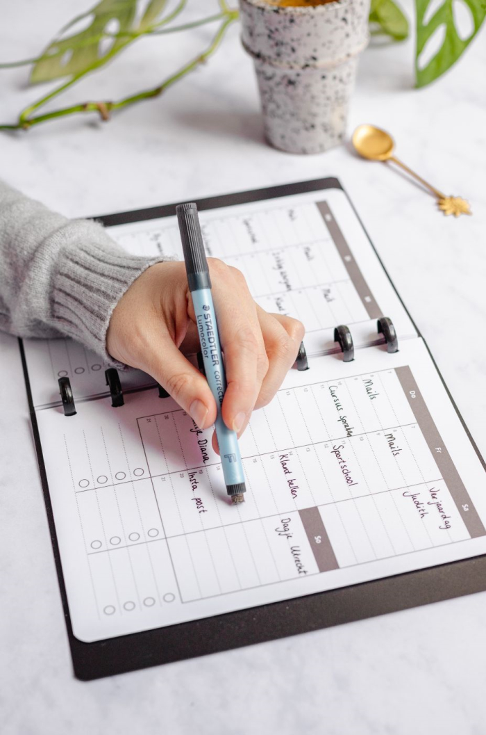 Hand erasing writing on calendar page with assorted items and marble in background