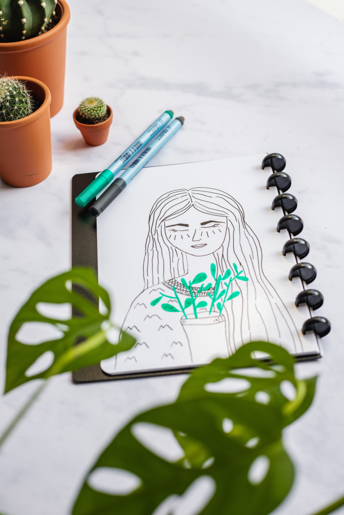Drawing of woman and plant in notebook with plants surrounding on a marble background
