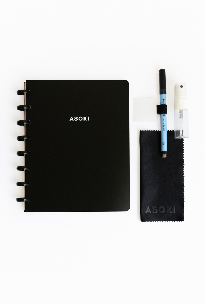 Asoki notebook with black cover next to black pen, pen loop, spray and cloth on white background
