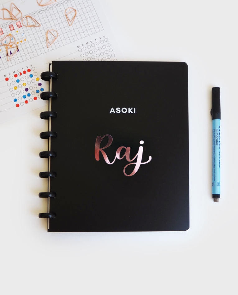 Customised Asoki black notebook with rose writing next to black pen