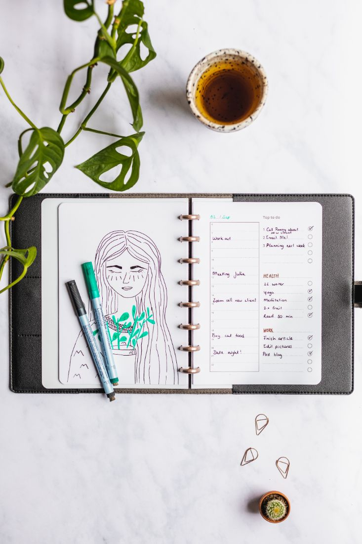 Open Asoki planner with black vegan leather cover on a marble background
