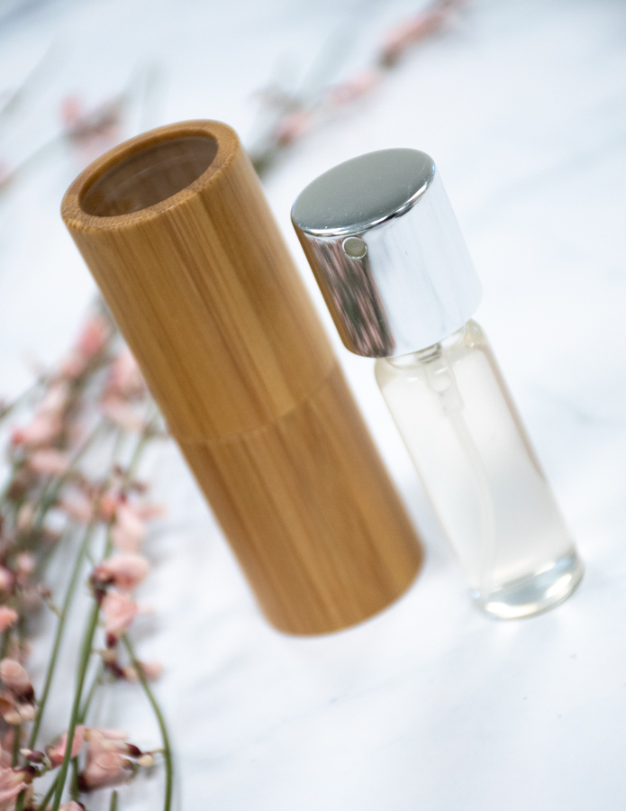 Bamboo cylinder next to glass spray bottle on marble background with flowers