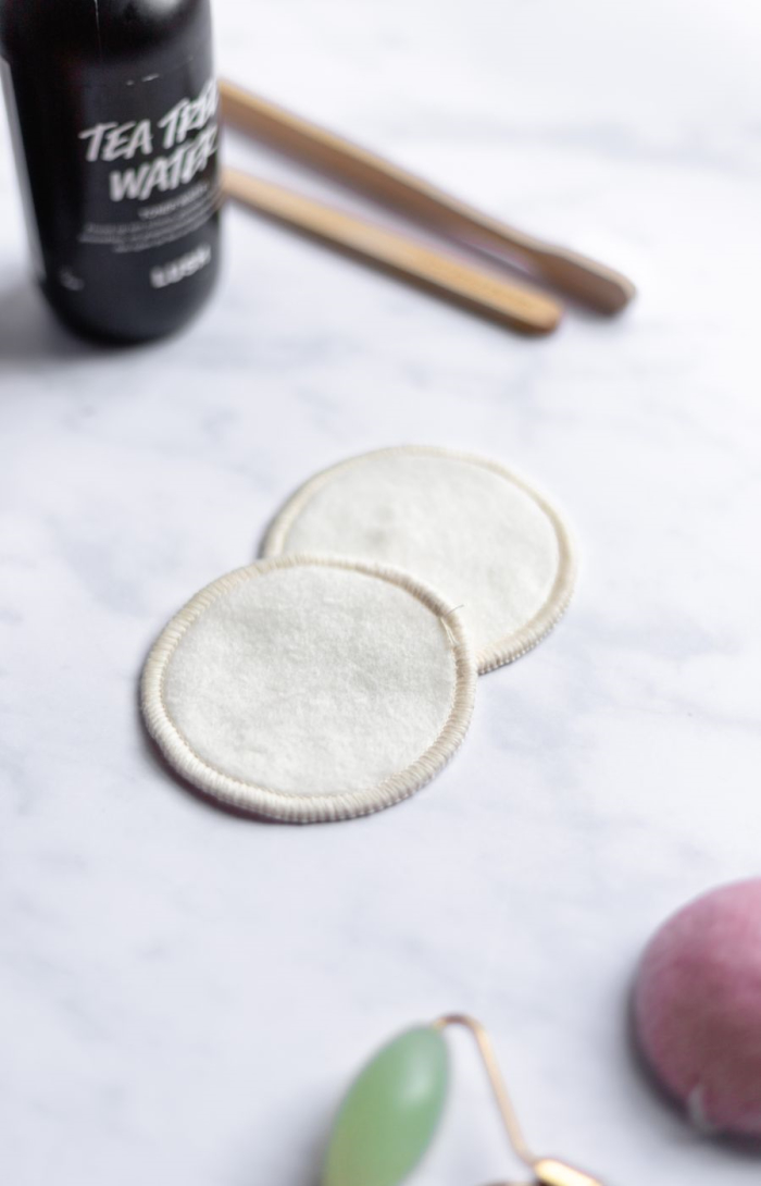 Two beige hemp make-up remover pads on marble background with assorted items surrounding
