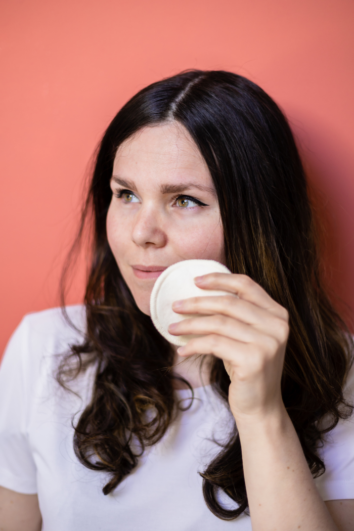 Woman using white hemp reusable makeup remover pads on orange background