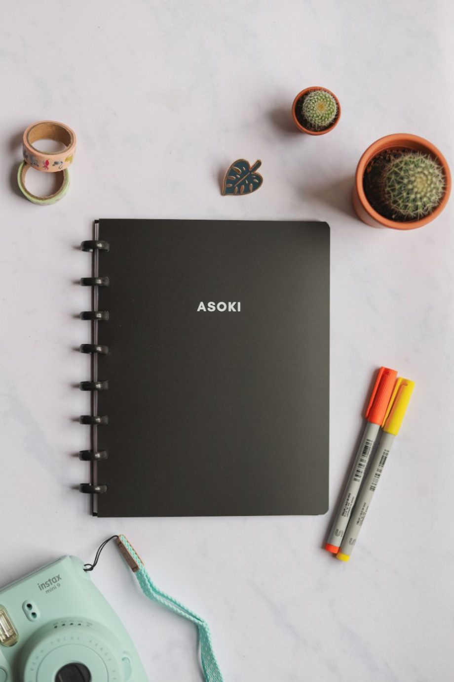 Black notebook with white letters next to assorted items on marble background