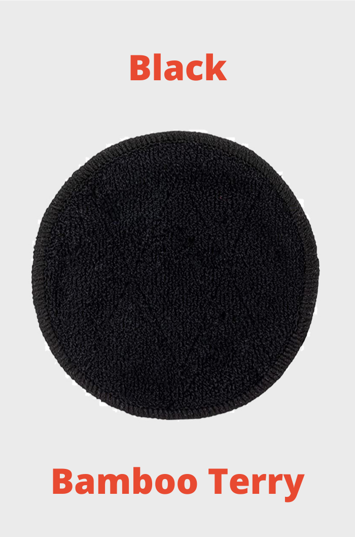 Round black reusable make-up remover pad made of bamboo and red text on grey background