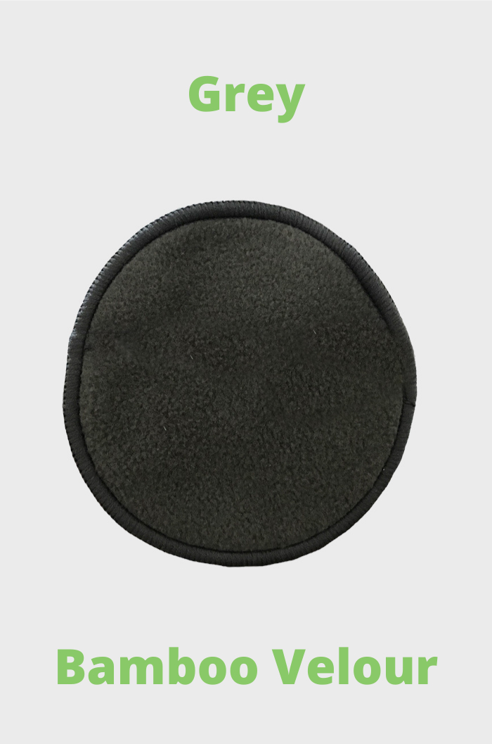 Round dark-grey reusable make-up remover pad made of bamboo and green text on grey background