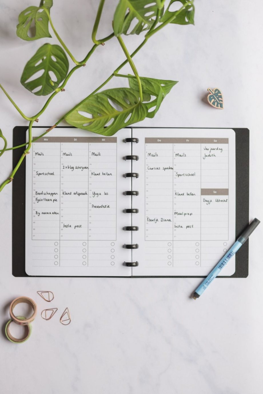 Vertical erasable monthly calendar with black pen next to assorted items on marble background