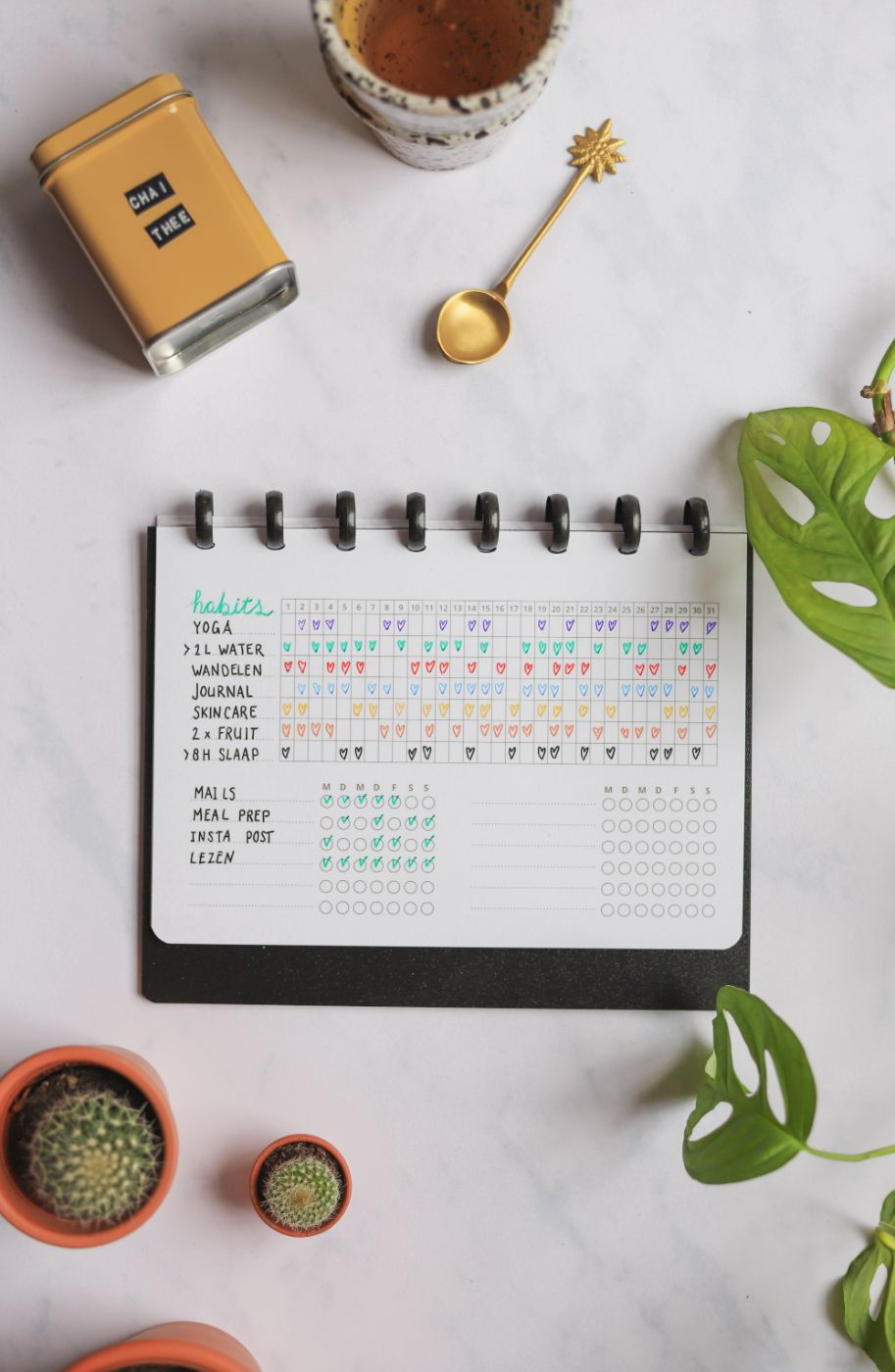 Erasable habit tracker next to assorted items on marble background