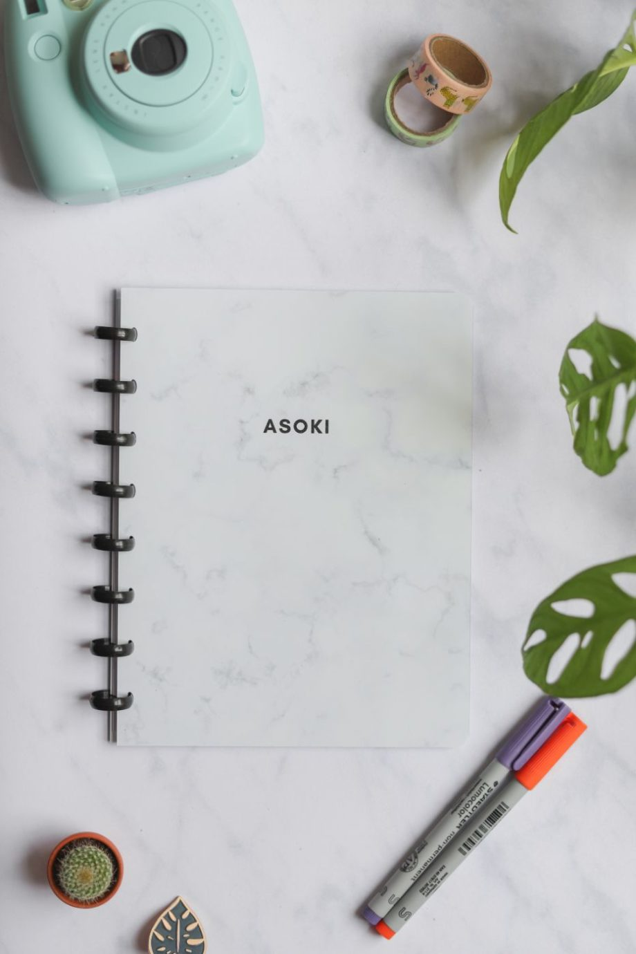 Erasable marble-covered notebook next to assorted items on marble background