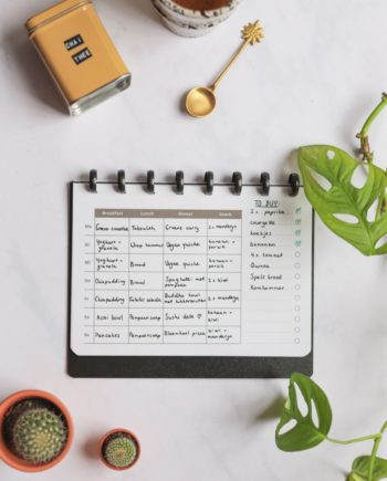 Erasable nutrition planner next to assorted items on marble background