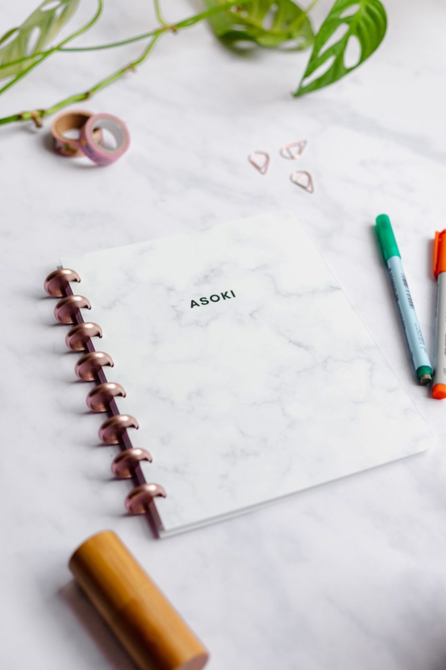 Asoki marble notebook with rose-gold metal discs next to bamboo spray and pens in orange and green on marble background