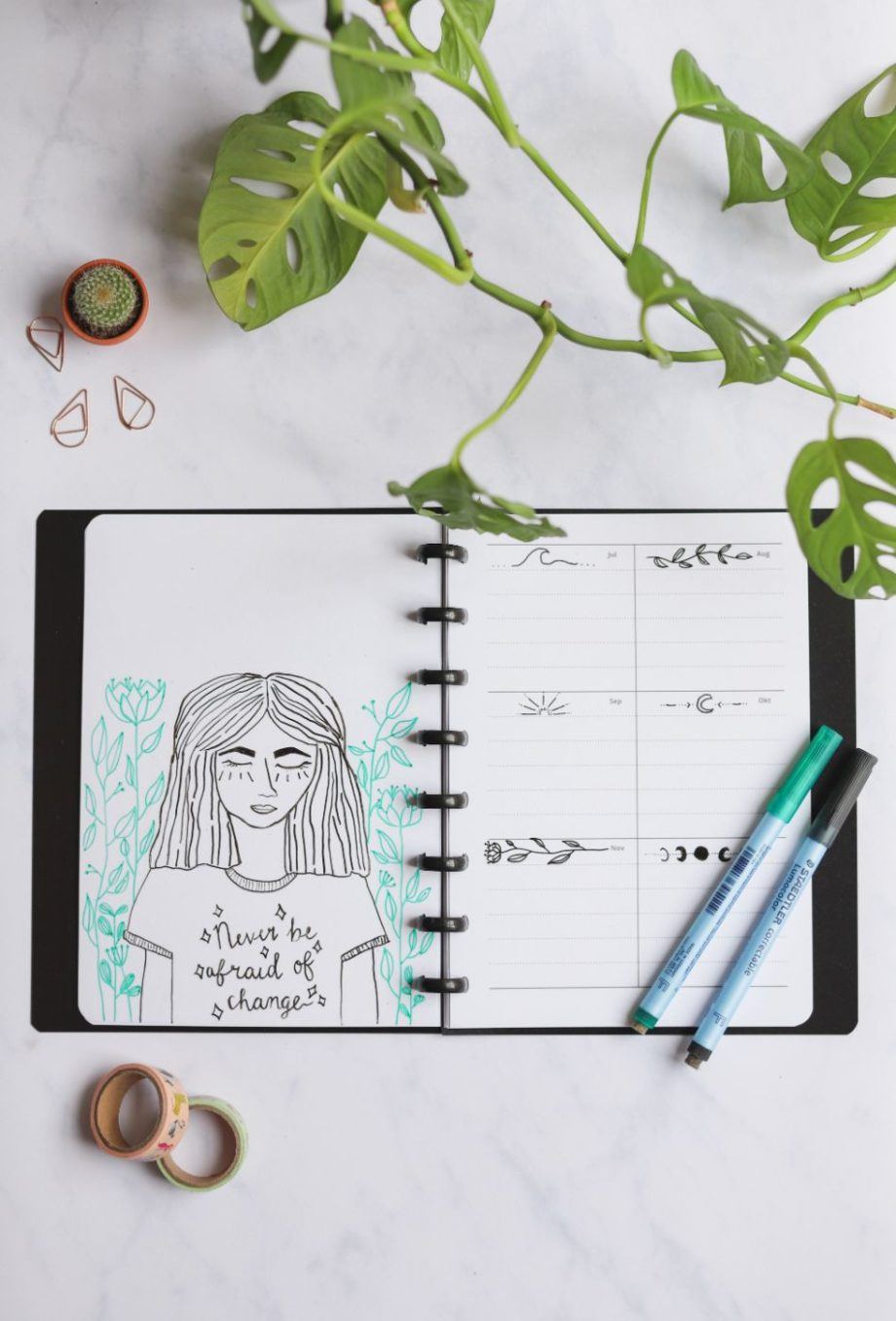 Erasable yearly calendar pages decorated with doodles in black vegan leather cover next to assorted items on marble background