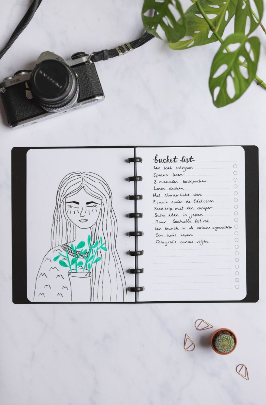 Erasable blank page with drawing of girl and erasable to-do list next to assorted items on marble background