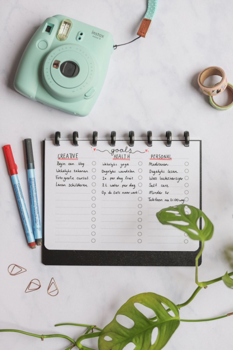 Horizontal erasable filled-in to-do list with black rings and black cover next to pens, camera and plant on marble background